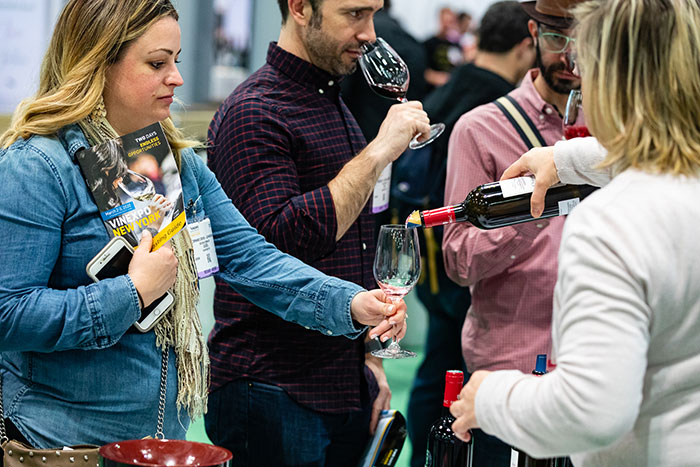 Day-1-Show-Floor-WOW-Exhibitor-Pouring-Wine
